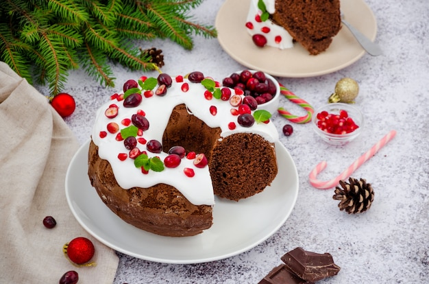 Chocolate cake christmas wreath with sugar icing, cranberries, pomegranate and mint leaves on top.