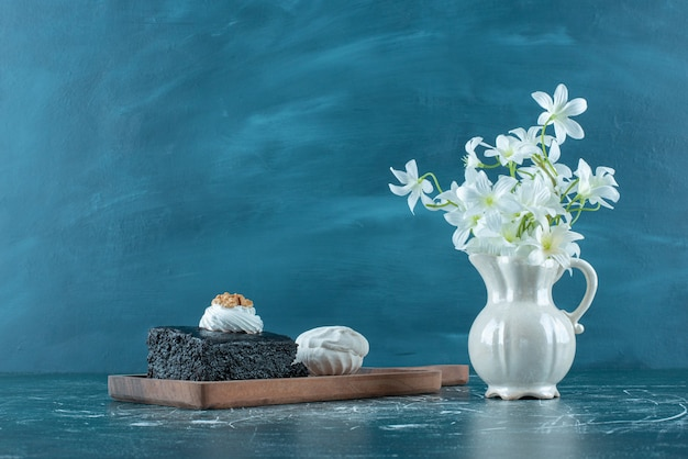 Chocolate cake, cookie and a vase of white lilies on blue.