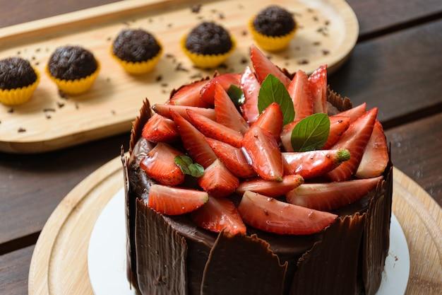 イチゴ、バジルの葉、ブラックベリージャムとその周りのチョコレートプレートで覆われたチョコレートケーキ。背景の准将(ブラジルの甘い)。