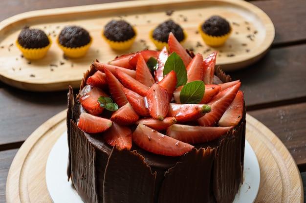 イチゴ、バジルの葉、ブラックベリージャムとその周りのチョコレートプレートで覆われたチョコレートケーキ。背景の准将(伝統的なブラジルの甘いもの)。