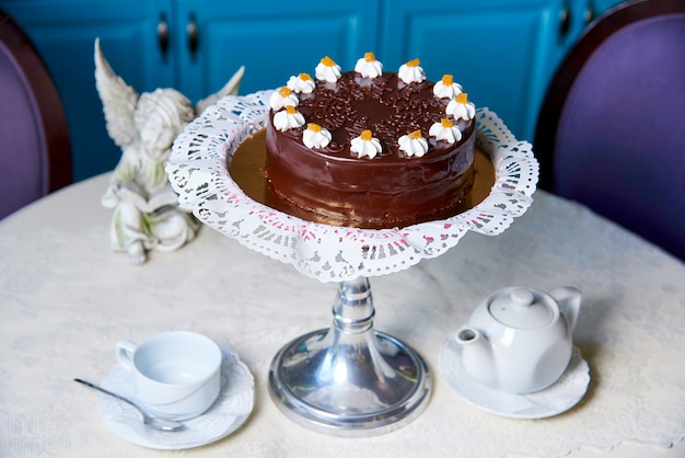 A chocolate cake on a decorated table.