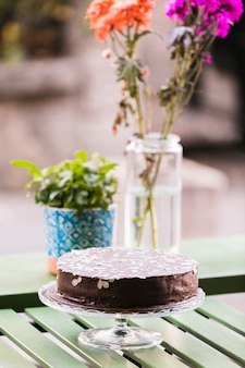 Chocolate cake decorated with almond slices on cake stand over table