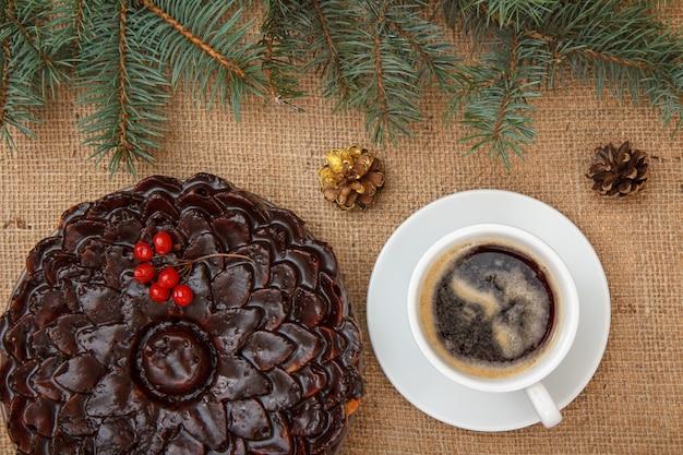 ガマズミ属の木の束、トウヒと荒布の枝とテーブルの上のコーヒーのカップで飾られたチョコレートケーキ。