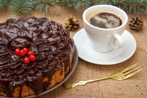 ガマズミ属の木の束、トウヒの枝、フォーク、荒布をテーブルに置いたコーヒーで飾られたチョコレートケーキ。
