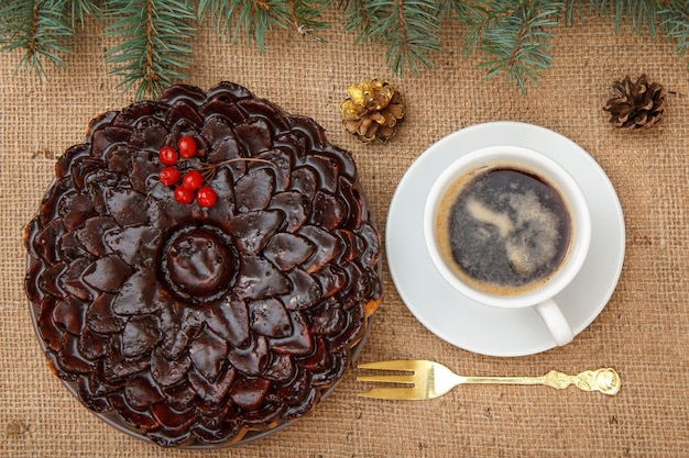 ガマズミ属の木の束、トウヒの枝、フォーク、荒布をテーブルに置いたコーヒーのカップで飾られたチョコレートケーキ。