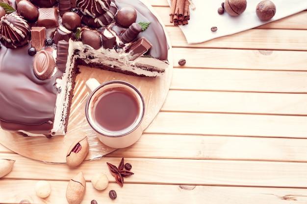 마카다미아 견과류와 커피 한 잔을 곁들인 초콜릿으로 장식된 초콜릿 케이크