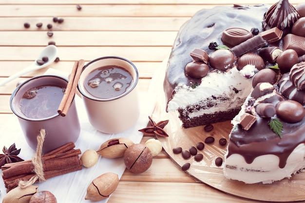 마카다미아 견과류와 커피 두 잔을 곁들인 초콜릿으로 장식된 초콜릿 케이크