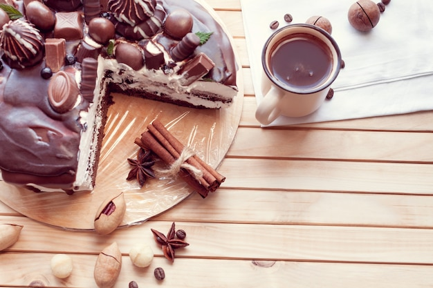Chocolate cake decorated with chocolates with macadamia nuts and a cup of coffee