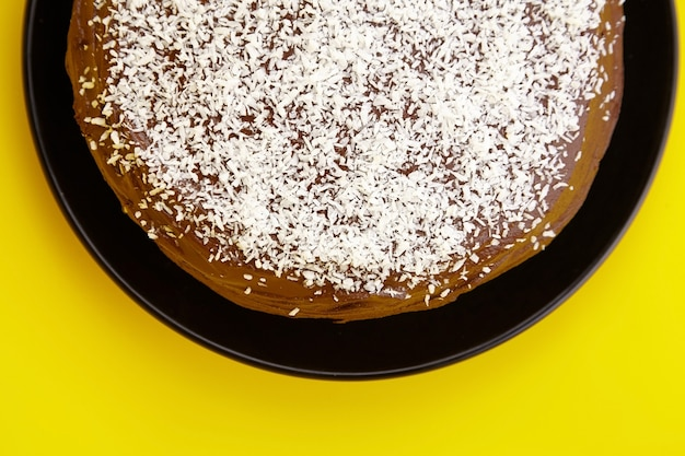 Chocolate cake decorated with flaked coconut, homemade pie on yellow background, top view. half of home cake with cocoa ingredient on black ceramic plate