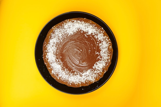 Chocolate cake decorated with flaked coconut, homemade pie on yellow background, top view. whole home cake with cocoa ingredient on black ceramic plate