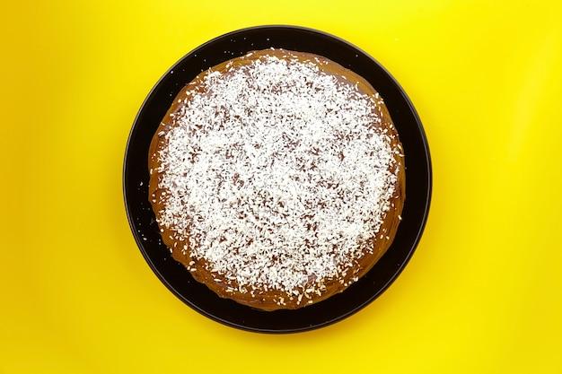 Шоколадный торт, украшенный кокосовой стружкой на желтом