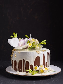 Chocolate cake decorated with flowers and poured white icing. copyspace