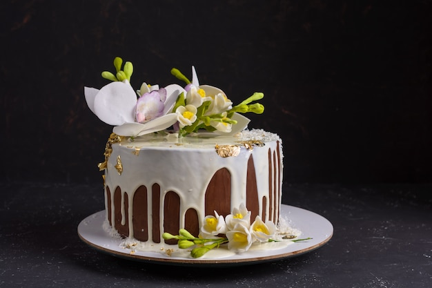 Chocolate cake decorated with flowers and poured white icing