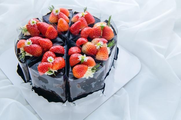Шоколадный торт, украшенный свежей клубникой на белой ткани, концепция торта и выпечки