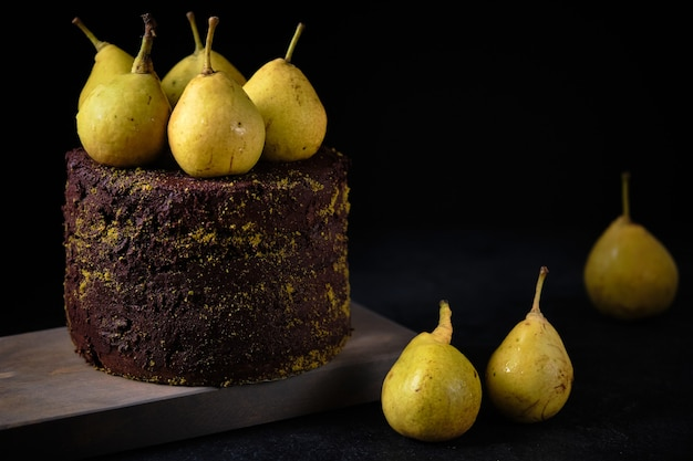 Шоколадный торт, украшенный молотыми фисташками и свежими грушами на деревянной доске.