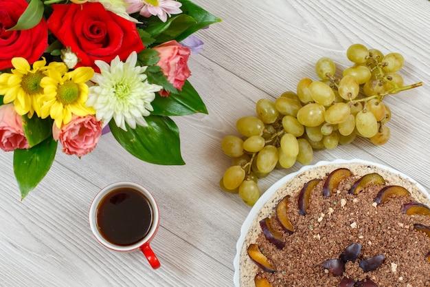 灰色の木の板にプラム、花の花束、ブドウ、コーヒーで飾られたチョコレートケーキ