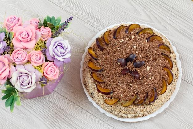灰色の木の板にプラムと手作りの花で飾られたチョコレートケーキ