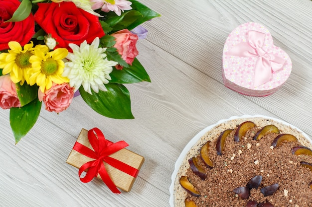 Chocolate cake decorated with plums, a bouquet of flowers and gift boxes on the gray wooden boards. top view.