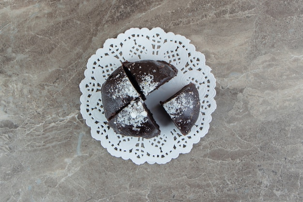 Chocolate cake divided into four pieces on marble surface