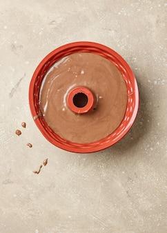 ベージュ色のキッチンテーブル、上面図のベーキングフォームのチョコレートケーキ生地