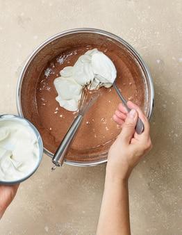 Процесс приготовления теста для шоколадного торта, добавление в тесто йогурта, вид сверху