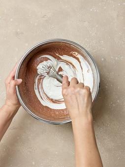 Процесс приготовления теста для шоколадного торта, замешивание йогурта в тесте, вид сверху