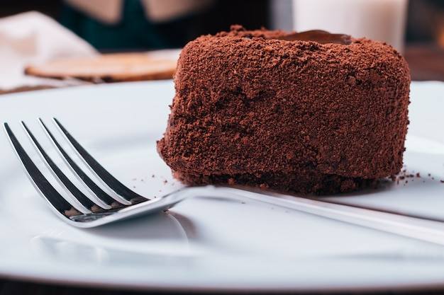Chocolate cake and fork on a white plate