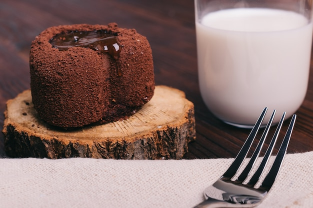 Chocolate cake and glass of milk on a brown table, fork on the tablecloth