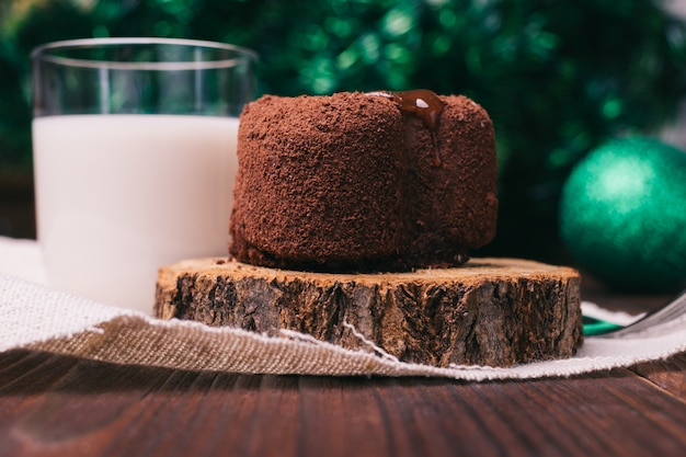 Chocolate cake, a glass of milk and christmas decorations on wooden table
