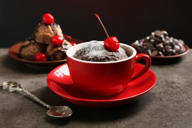 위에 체리와 붉은 머그잔에 초콜릿 케이크를 닫습니다.