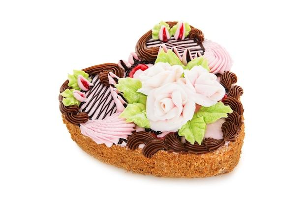 分離されたクリーム色の花で飾られたハートの形のチョコレートケーキ