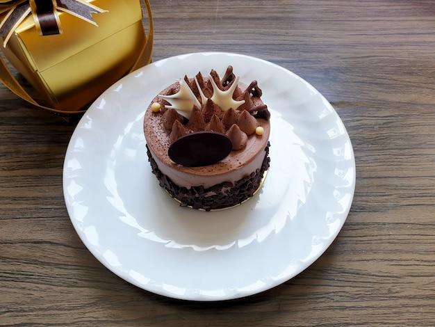 木製の背景に白いプレートのチョコレートケーキ