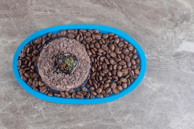 大理石の表面にコーヒー豆がいっぱい入った大皿にチョコレートケーキ