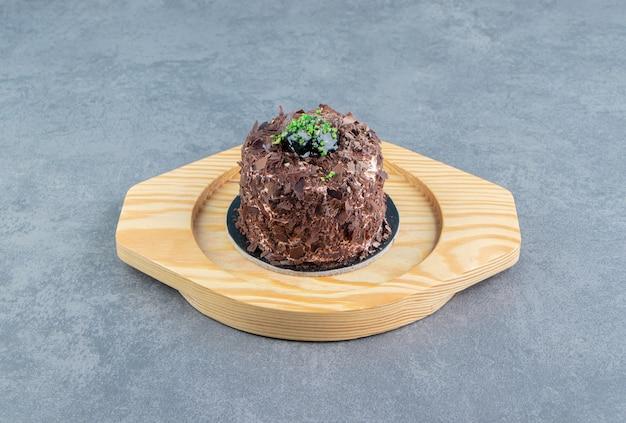 나무 접시에 초콜릿 케이크입니다.