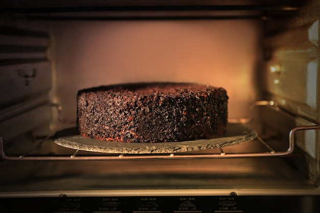 Chocolate cake in oven, close up