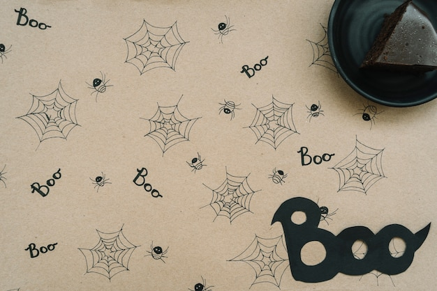 Chocolate cake on paper with web and spider background