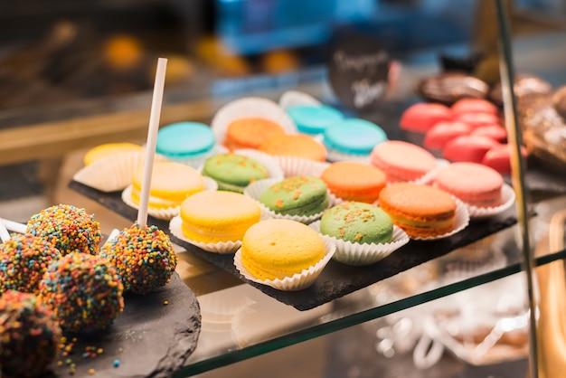 디스플레이 캐비닛에 다채로운 뿌리와 마카롱이 든 초콜릿 케이크