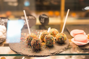 Chocolate cake pops with colorful sprinkles in the display cabinet