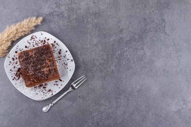 흰 접시에 카카오 가루를 넣은 초콜릿 케이크를 돌 테이블에 놓습니다.