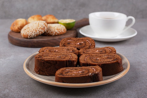 Rotolo di torta al cioccolato su piatto in ceramica con tè nero