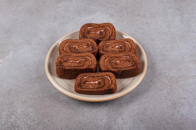 Rotolo di torta al cioccolato su piatto in ceramica