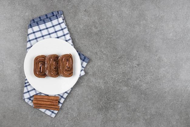 シナモンと白いプレートにチョコレートケーキロール