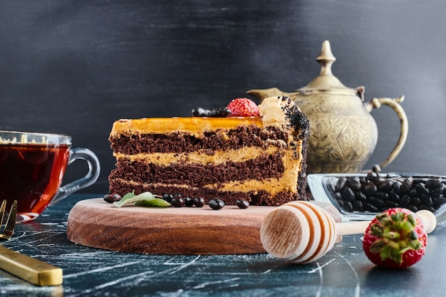 Шоколадный торт подается со стаканом чая.