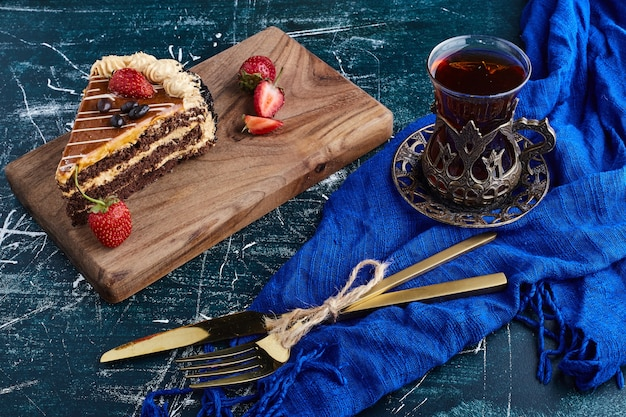 Chocolate cake served with strawberries on blue background with a glass of tea.