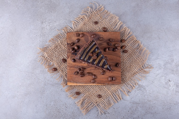 Chocolate cake slice with coffee beans placed on sackcloth surface .