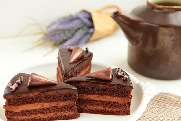 휘핑 크림과 함께 흰색에 컬이 있는 초콜릿 케이크 조각. 초콜릿을 곁들인 맛있는 토핑 슬라이스