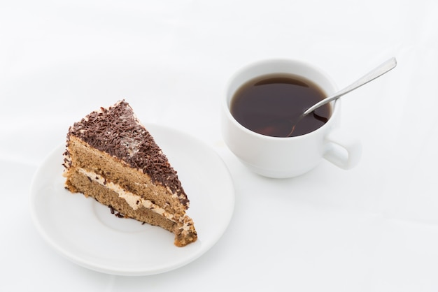 Chocolate cake slice with curl on white dish with hot drink