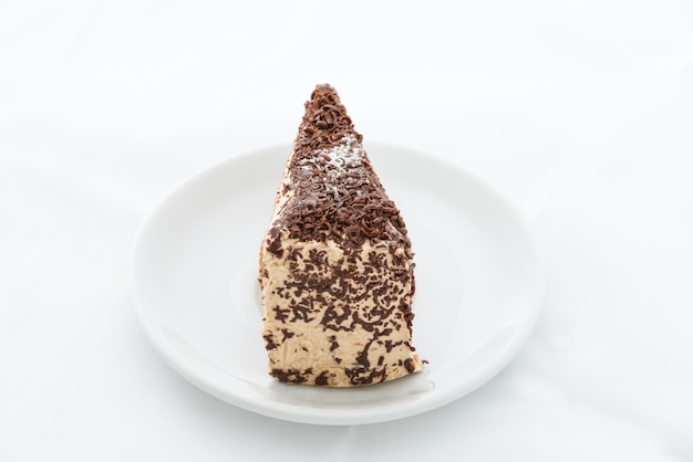 Chocolate cake slice with curl on white dish