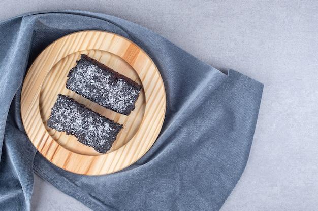 대리석 테이블에 수건에 나무 플래터에 초콜릿 케이크 조각.