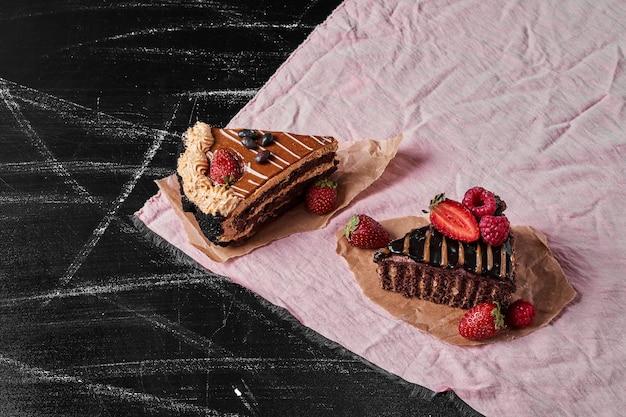 Ломтики шоколадного торта на черном
